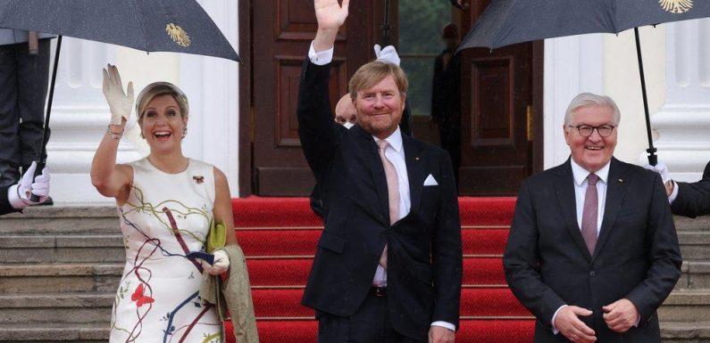 Máxima und Willem-Alexander grüßen in Berlin unterm Regenschirm